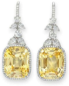 Yellow sapphire and diamond earrings. Each suspending a cushion-cut yellow sapphire, weighing approximately 14.03 and 13.83 carats, within a circular-cut diamond surround, joined by a graduated pear and circular-cut diamond foliate link, to the circular-cut diamond hoop, mounted in platinum. Via Diamonds in the Library.