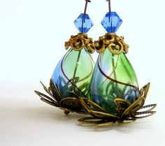 """""""The transparent blue and green tear drop hand blown glass bead is nestled in several layers of brass leaves, resting peacefully on a brass lily pad, and topped with a brass flower bead cap and a cobalt blue Swarovski bicone crystal, forming a lotus flower"""""""