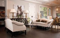 Chic, elegant living room design with white camel back sofas, chocolate brown velvet pillows, espresso Elisabeth mirrored cabinet buffet, Z Gallerie Winter Stallion Giclee, brass cocktail table, coffered ceiling and gray walls paint color.