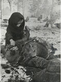 A child looks at the corpse of his mother who has been murdered at the Ozarichi concentration camp in Belarus.
