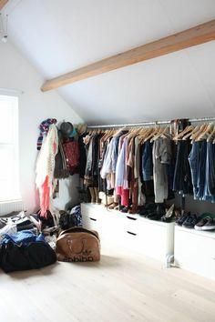 rangement dans un dressing mansarde avec espace ouvert et placards blanc au sol