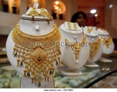 A saleswoman stands behind the showcased gold necklaces at a jewellery showroom in Agartala, capital of India's northeastern state of Tripura, August 18, 2010. India's gold buying edged up for a second day on Wednesday as international prices steadied, with traders eyeing the rupee for direction, dealers said. REUTERS/Jayanta Dey (INDIA - Tags: BUSINESS) - Stock Image
