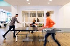 Stockfoto : Blurred motion of business people playing table tennis in creative office