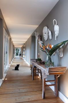 A long hallway, in which resident pup Bella lounges, connects the living rooms and kitchen areas with the bedrooms. Masks from the African Market in Johannesburg adorn the wall.
