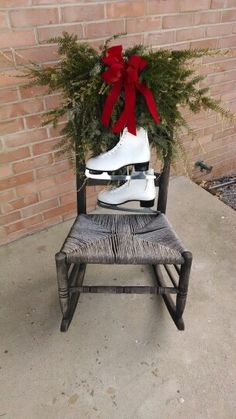 Vintage rocking chair decorated for Christmas with fresh pine, ice skates and red velvet bow.