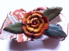 Broche en forma de rosa, hecho con piel teñida y modelada a mano.