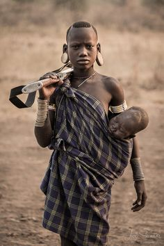 Young Mursi woman carrying a baby and a rifle. Omo valley, Ethiopia. © Joel Santos - Photography