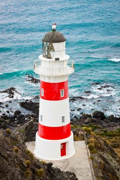 Lighthouse at Cape Palliser. New Zealand Lighthouse Storm, Lighthouse Art, Lighthouse Keeper, Lighthouse Lighting, Lighthouse Pictures, Beautiful Lights, Beautiful Places, New Zealand Holidays, Beacon Of Light