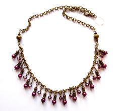 Halsband i brons med vinröda kristaller och odlade pärlor. Längd: 50cm