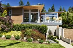 This elegant 4,600 square feet home is situated on a slope and sits back from the street, providing a classic, timeless, and understated presence. Concrete and cedar create a pleasant contrast to the lush greenery surrounding the home.