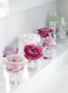 Such a cute way to display blooms - cut down single roses and place them in short, clear vases.