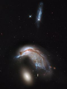 The Porpoise Galaxy from Hubble Image Credit: NASA, ESA, and The Hubble Heritage Team (STSci/AURA)  Just a few hundred million years ago, NGC 2936, the upper of the two large galaxies shown, was likely a normal spiral galaxy... then it got too close to the massive elliptical galaxy NGC 2937 below and took a dive. Dubbed the Porpoise Galaxy for its iconic shape, NGC 2936 is not only being deflected but also being distorted...