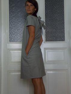 Becasina v šedé mašli Minimalisticky řešené šaty z šedé bavlny. Vzadu s vázačkou a rovným průstřihem. Rovného až áčkového střihu. A s nepostradatelnými kapsami, tentokrát v zelenkavé. Velikost M.