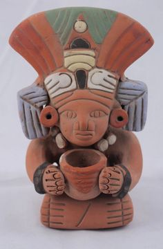 """Mexican Ceramic Figurine of Mayan/ Aztec Holding Pot w Head Piece  7"""" Tall.  The figurine is wearing an amazing head piece, depicting feathers and and other designs.  The figurine is wearing earrings and a white necklace.  The arms are decorated with black bracelets."""