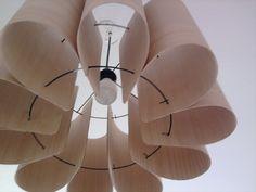 """Como una forma de crear una propuesta innovadora con materia prima nacional, el joven diseñador chileno Felipe Vega diseñó una exclusiva lámpara llamada """"Dalia"""". Se utilizo Surflex, con chapas de maderas diferentes por ambas caras, además de un soporte metálico."""