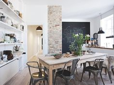 Great little kitchen with modern and vintage elements intertwined. The brick pillar is a standout. Love the angle of the table and the industrial charis against the warm timber table.