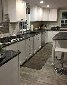 White kitchen cabinets with black countertops wood floor black granite kitchen gray wood floors kitchen ideas . Black Granite Kitchen, White Cabinets White Countertops, Grey Kitchen Cabinets, Kitchen Redo, New Kitchen, Dark Cabinets, Dark Kitchen Countertops, Kitchen Ideas, Maple Cabinets