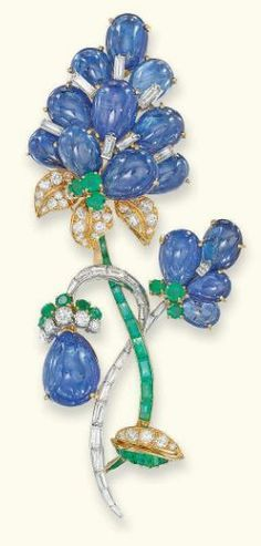 A SAPPHIRE, DIAMOND AND EMERALD BROOCH, BY MAUBOUSSIN Designed as a series of graduated cabochon-cut sapphire petals with vari-cut diamond and emerald accents to the pavé-set diamond leaves and baguette-cut diamond and emerald stems, 9.1 cm high, with French assay marks for platinum and gold Signed Mauboussin Paris, No. 15600 (indistinct)