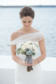 Oceanside, the lovely bride gazes upon her exquisite bouquet wrapped in her grandfather's tie.