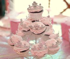 Pink frosted cupcakes baked in silver foil liners, then topped with tiny tiaras and presented in a cupcake display stand.  Perfect for a Princess party.