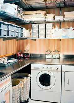 A stainless-steel counter above the front-loading washer and dryer offers extra space for folding and sorting clothes. Pink-striped wallpaper takes the edge off the industrial materials. Glass jars on the counter attractively store detergent. Rolling laundry bins under the counter make quick work of sorting clothes into light or dark loads.