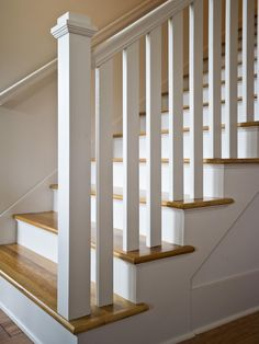A square post and double handrail lead the way up this white, wooden staircase with natural wood steps.