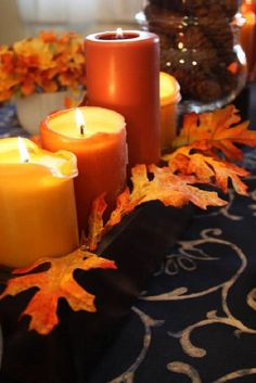 fall tablescape with black tablecloth and orange candles