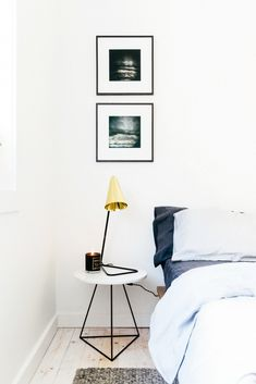Modern bedside table with brass lamp in white bedroom.