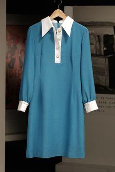Vestido azul com botões dourados e punhos em branco, de Cidália na série Depois do Adeus