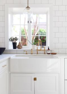 White simplicity in the kitchen: white cabinetry with a farmhouse sink and white subway tile backsplash. I love how the window is slightly offset from the sink, an endearing quirk of a historic house. A Colonial Home with a Contemporary Twist - Home Tour - Lonny