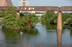 A kayaker passes by the fun and inspiring graffiti paintings on the Austin Railroad Graffiti Bridge over Lady Bird Town Lake, Austin, Texas....