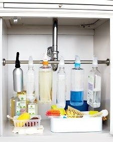 Organize under the kitchen sink by hanging spray bottles across a curtain rod.