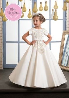 Simple, yet elegant Stockton dress for weddings enhances the beauty of any flower girl. This A-line satin dress features a jewel neckline, short sleeves, natural waist trimmed with bows, and a full box pleated skirt. A V-cut back and a zipper closure added for easy dressing. Gorgeous lace appliques accent the chest, the back, and the top of the skirt for finishing touch.