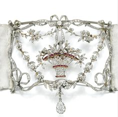 Ruby and diamond plaque de cou, circa 1905. Centering on a giardhetto millegrain set with calibré cut rubies and rose diamonds within a frame of ribbon, bow and floral sway design similarly set with rose diamonds, suspending a pear shaped diamond drop to a wide moíré silk ribbon