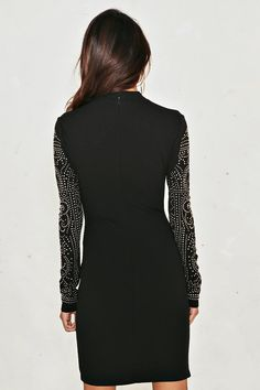I've got chills, they're multiplying. The Tell Me About It Studded Dress features a high neckline, bodycon, mini silhouette, zip closure at back, and studded detailing at front and sleeves.