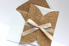 I like the embossed fold over and matching liner. Maybe in Coral? Wedding Invitations Gold embossed and cream by AlexandriaLindo, $8.00