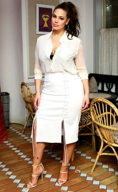 ASHLEY GRAHAM wears a cream button-down blouse with a white lace-up high-waisted skirt and strappy beige sandals