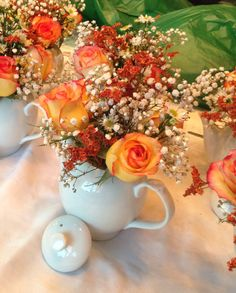 """Teapot Centerpieces. These centerpieces were created for a country wedding. It was made with hybrid roses, baby breath and wild daisies. Some orange painted wild grass gives the centerpiece a """"fall season ambiance"""", perfect for a country wedding."""