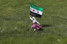 A Syrian refugee runs with a Syrian opposition flag during a demonstration against President Assad, outside the Syrian embassy in Amman.