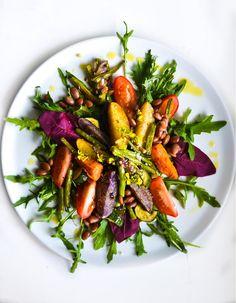 Salat aus würzigen Kartoffelspalten, gemischten Bohnen, Rucola und Cajun Spices
