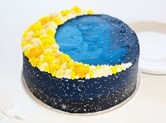 The side view of a dark blue galaxy cake with a moon piped on top!