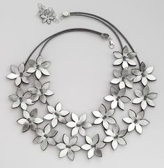 Silver Leather Flowers All Around - Eninaj: Two rows of silver flowers which can be pushed together or separated on a leather string with an omega clasp.