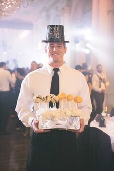 Dessert Server in New Year's Eve Party Hat |   Photography: Rob and Wynter Photography.   Read More:  http://www.insideweddings.com/weddings/mlb-players-white-black-gold-nye-ballroom-wedding-in-atlanta/806/