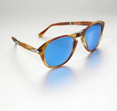 "A pair of 1960s-era 'foldable' sunglasses with plastic tortoise shell-like frames and blue lenses; inside right arm reads ""Persol;"" inside left arm reads ""brevett"" and ""Ratti"" (last name of the Italian photographer, Giuseppe Ratti, who invented this eyewear in the 1910s)."