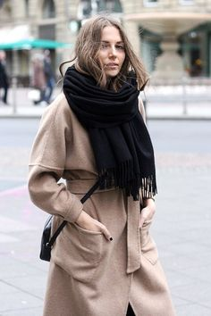 Vanja wears an oversized black scarf over her wrap camel coat. This blogger confirms that you can never go wrong with pairing black and camel!