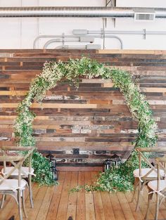 Circle arch (or other type of arch) with greenery against light wall. Will put glass table inside after ceremony to hold cake