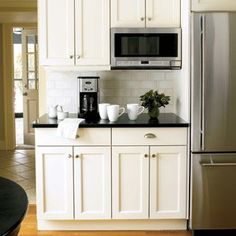 Black counter tops, white cabinets & stainless steel appliances