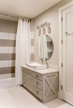 In-law master greige bathroom features grey vanity, white quartz countertop and striped white and grey shower tile.- Timber Frame Home with Farmhouse