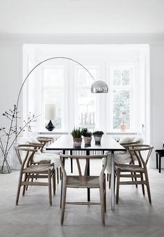 This stunning dining room features the FLOS Arco floor lamp, wishbone chairs and large windows to let in sunlight.
