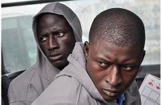 En busca de la verdad sobre 15 cadáveres a 523 kilómetros de Ceuta, por Patricia Gardeu. Foto de Fidel Raso: Dos inmigrantes conducidos a comisaría en Ceuta, en julio de 2013
